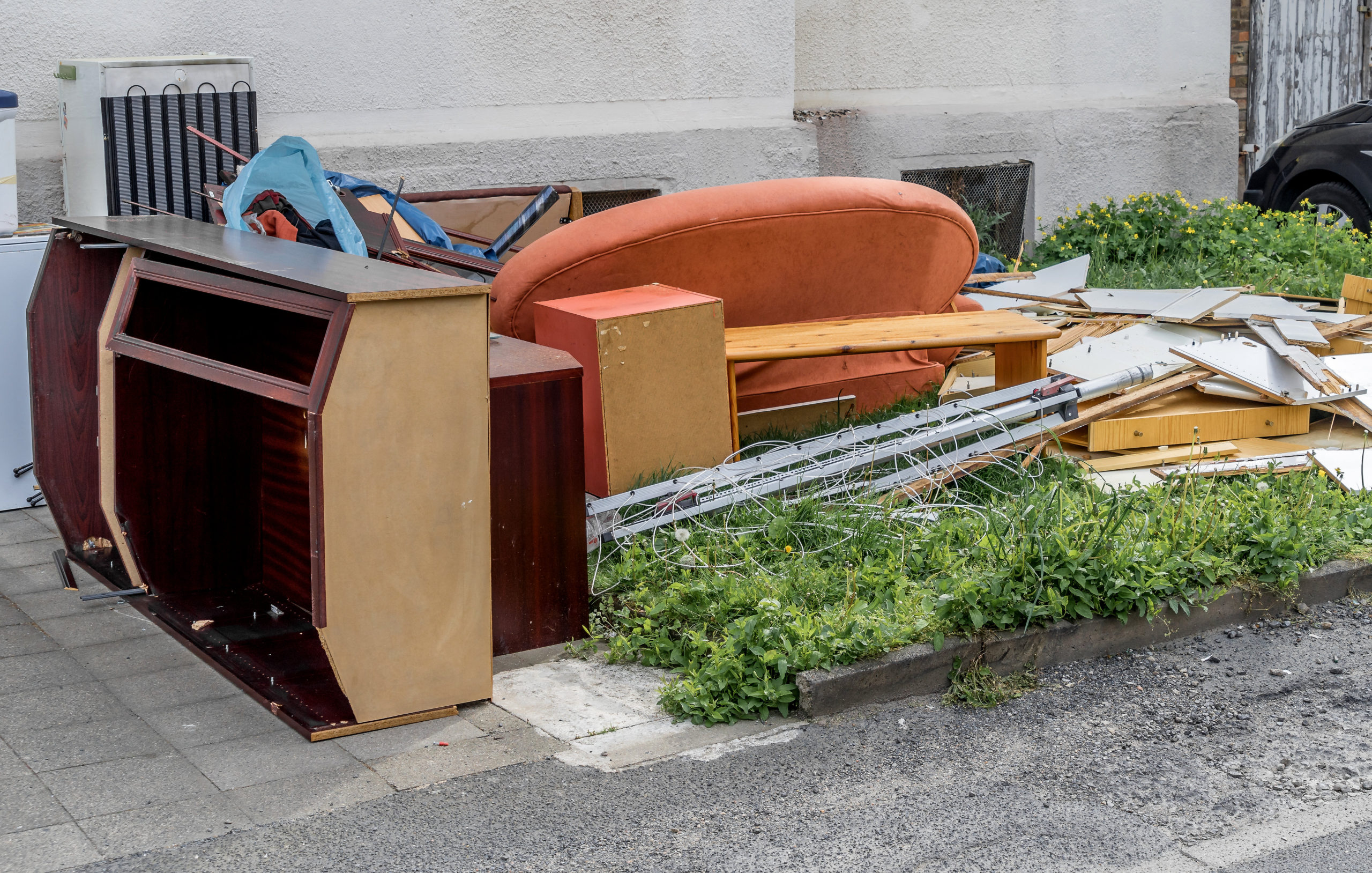 Bulky waste with cupboards, a sofa and furniture on the lawn in front of an apartment building, germany